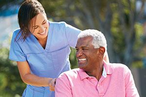 A caregiver pushes an older man in a wheelchair